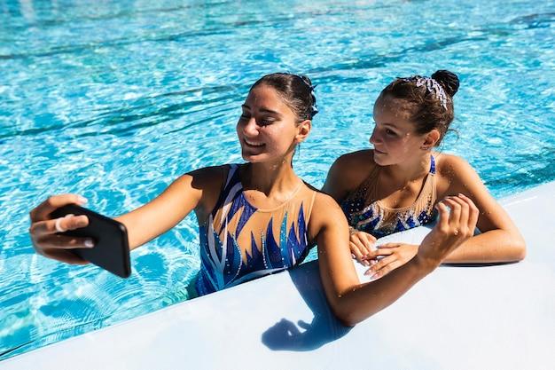 Jovem sorridente tirando uma selfie na piscina