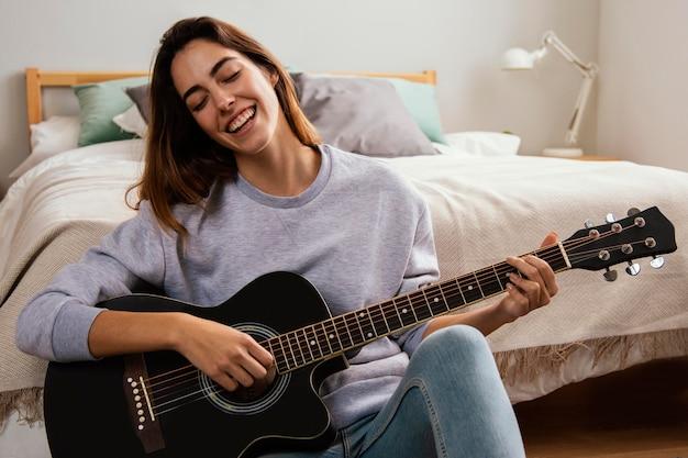 Jovem sorridente tocando violão em casa