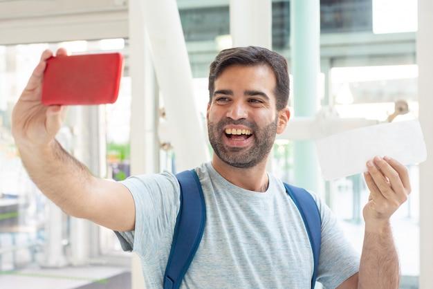 Jovem sorridente tomando selfie com bilhete a sorrir