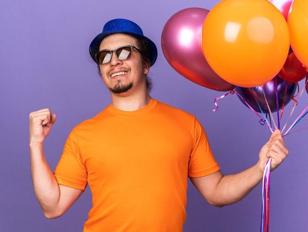 Jovem sorridente usando chapéu de festa com óculos segurando balões mostrando um gesto de sim isolado na parede roxa