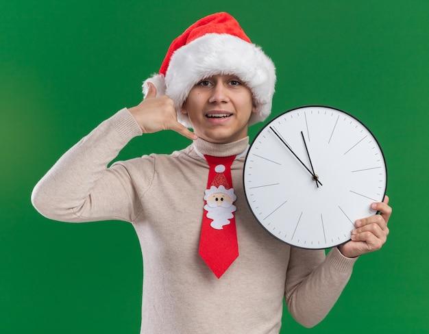 Jovem sorridente usando chapéu de natal com gravata segurando um relógio de parede mostrando um gesto de ligação isolado na parede verde