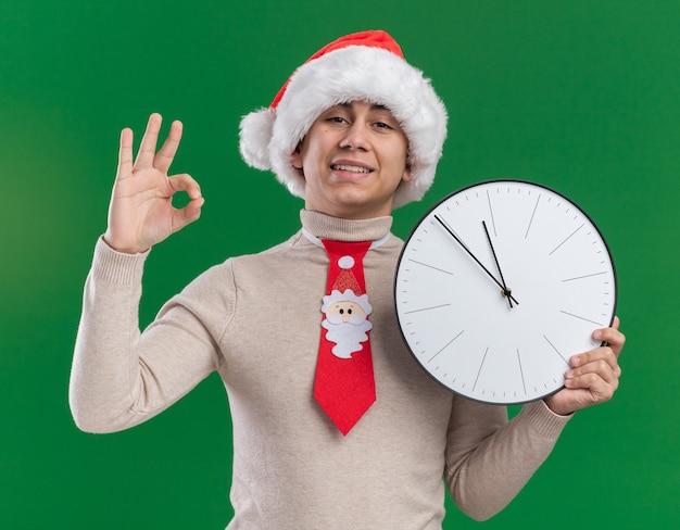 Jovem sorridente usando chapéu de natal com gravata segurando um relógio de parede mostrando um gesto de ok isolado na parede verde