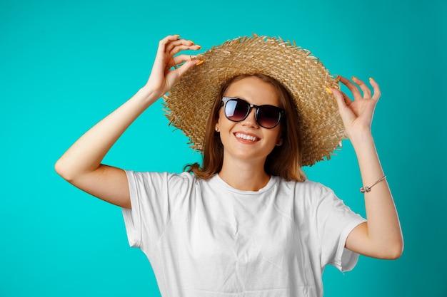 Jovem sorridente usando chapéu de palha e óculos escuros contra o azul