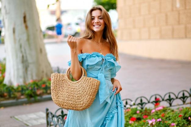 Jovem sorridente, usando um elegante vestido azul e uma bolsa de palha, caminhando pelo centro da cidade