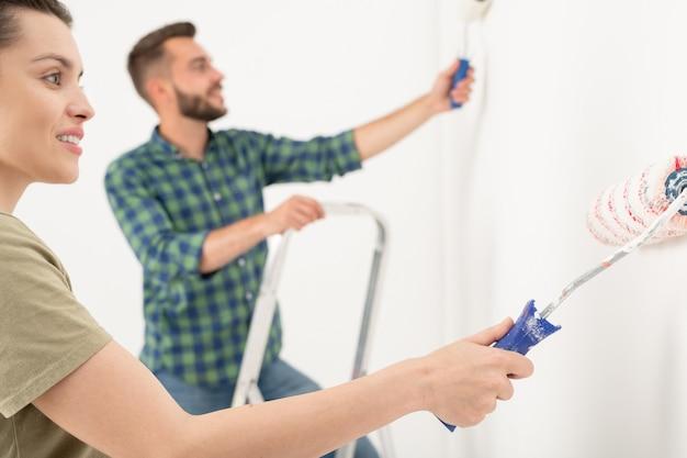 Jovem sorridente varrendo o rolo de pintura na parede enquanto pinta a sala com o namorado