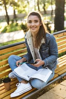 Jovem sorridente, vestindo uma jaqueta, sentada em um banco do parque, lendo uma revista