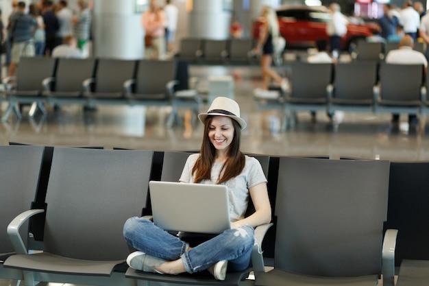 Jovem sorridente viajante turista mulher de chapéu sentada com as pernas cruzadas, trabalhando em um laptop, esperando no saguão do aeroporto internacional