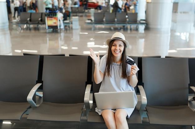 Jovem sorridente viajante turista trabalhando em um laptop segurando um cartão de crédito, espalhando as mãos, esperar no saguão do aeroporto internacional