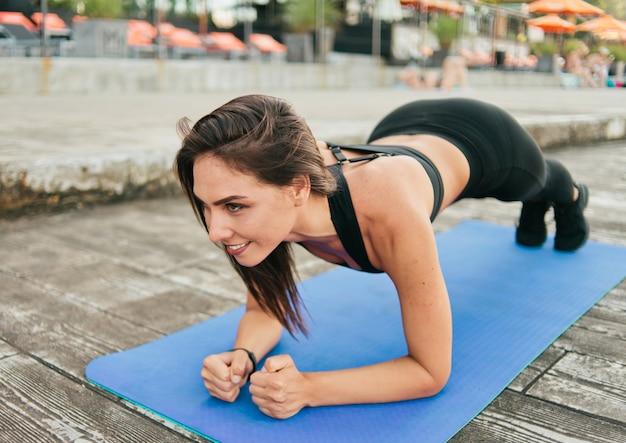 Jovem sorrindo apta para mulher em roupas esportivas fazendo exercícios de prancha na esteira ao ar livre