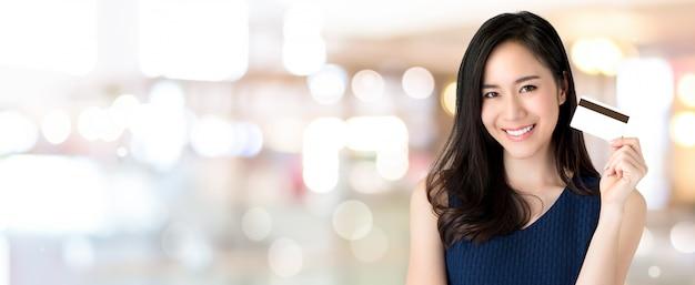 Jovem, sorrindo, bonito, mulher asian, apresentando, cartão crédito, em, mão