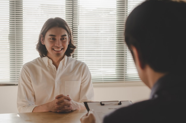 Jovem, sorrindo durante a entrevista de emprego e explicando sobre seu perfil com o gerente de rh de negócios segurando o currículo e sentado na sala de reuniões no escritório