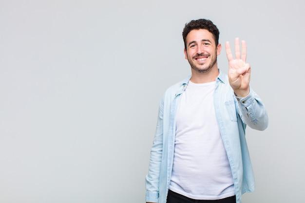 Jovem sorrindo e parecendo amigável, mostrando o número três ou terceiro com a mão para a frente, em contagem regressiva