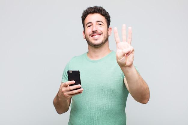 Jovem sorrindo e parecendo amigável, mostrando o número um ou o primeiro com a mão para a frente, em contagem regressiva Foto Premium