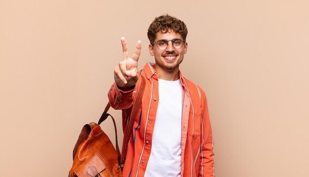 Jovem sorrindo e parecendo feliz, despreocupado e positivo, gesticulando vitória ou paz com uma mão. conceito de estudante