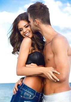 Jovem sorrindo e se abraçando com o namorado, ele beijando-a na bochecha. cabelo longo bonito ondulado, visual moderno
