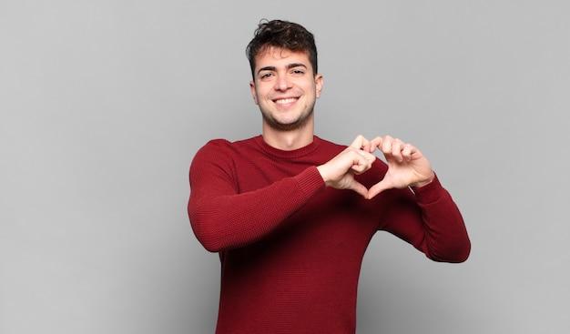Jovem sorrindo e se sentindo feliz, fofo, romântico e apaixonado, fazendo formato de coração com as duas mãos