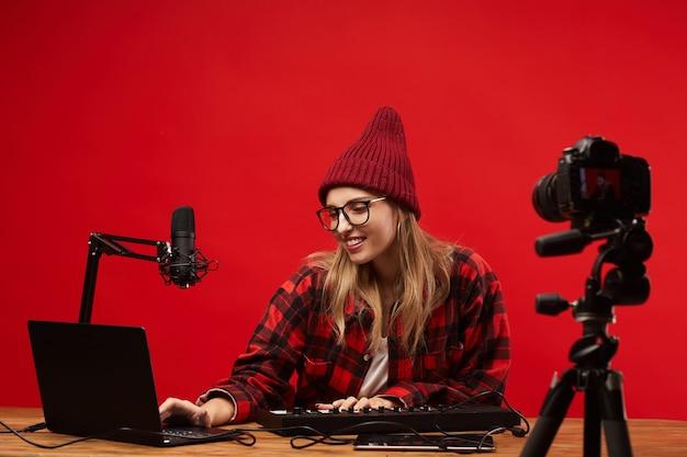 Jovem sorrindo e sentada à mesa e usando o laptop, ela gravando seu blog musical