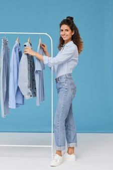 Jovem sorrindo em pé perto do cabide com roupas jeans contra o fundo azul
