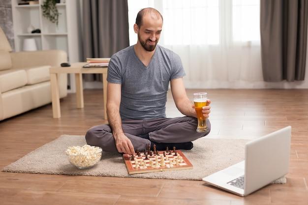Jovem sorrindo enquanto joga xadrez com amigos na videochamada.
