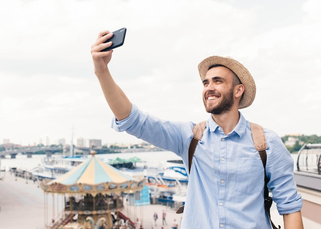 Jovem, sorrindo, homem, segurando, telefone pilha, e, levando, selfie, ao ar livre