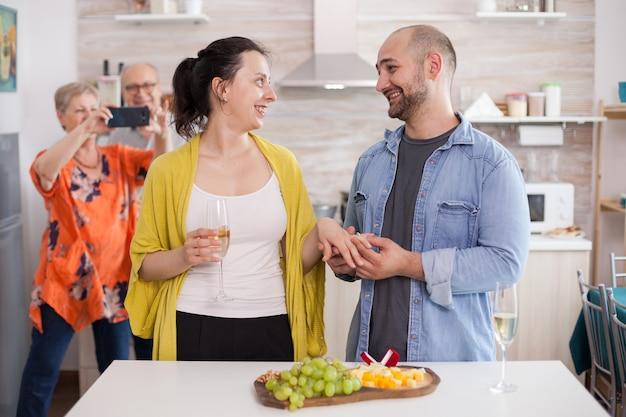 Jovem sorrindo para a esposa enquanto colocava o anel de noivado no dedo na frente dos pais durante o almoço em família.