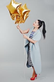 Jovem sorriu mulher com balões de ouro
