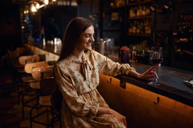 Jovem sozinha com um copo de vinho tinto, sentada no balcão do bar. uma pessoa feminina em um bar, emoções humanas, atividades de lazer, vida noturna