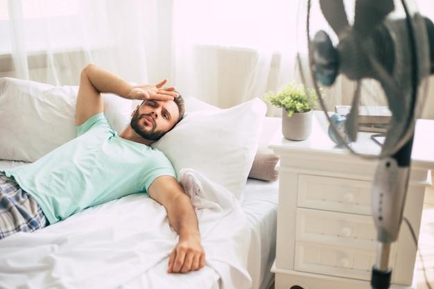 Jovem suado está tentando se refrescar do calor com um ventilador enquanto está deitado na cama em casa.