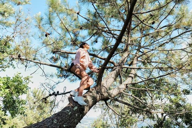 Jovem subindo em um pinheiro e parecendo relaxada, apenas uma garota