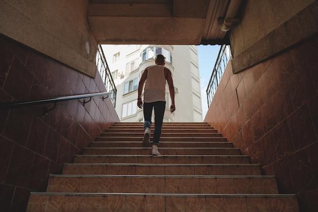 Jovem subindo escadas no metrô para pedestres
