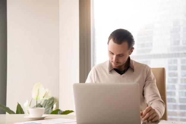 Jovem, sucedido, homem negócios, trabalhando, em, escrivaninha escritório, usando, laptop, computador