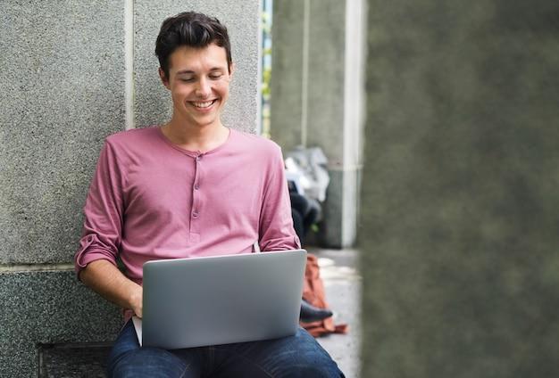 Jovem, sujeito, percorrendo, laptop, campus, conceito