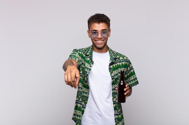 Jovem sul-americano apontando com um sorriso satisfeito, confiante e amigável, escolhendo você