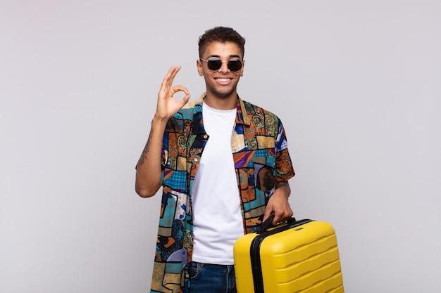 Jovem sul-americano se sentindo feliz, relaxado e satisfeito, mostrando aprovação com gesto de ok, sorrindo