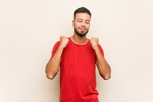 Jovem sul-asiático, levantando o punho, sentindo-se feliz e bem sucedido. conceito de vitória