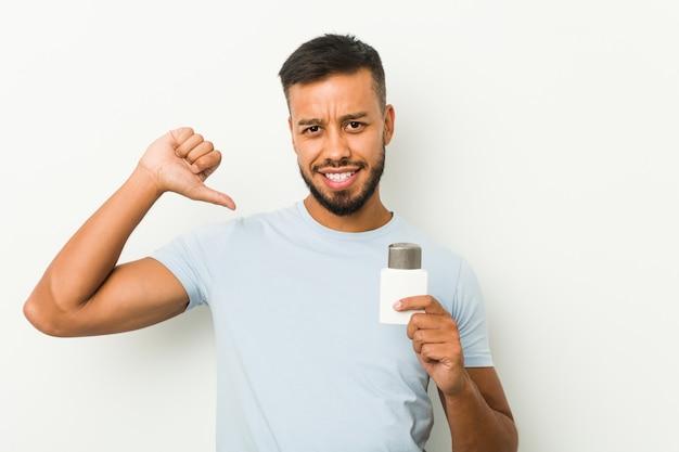 Jovem sul-asiático segurando um creme após barba se sente orgulhoso e auto-confiante, exemplo a seguir.