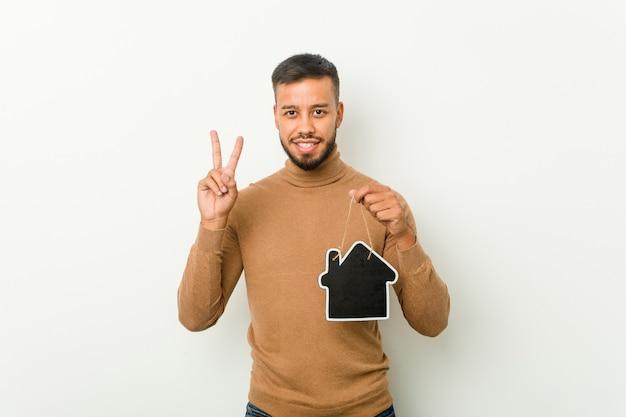 Jovem sul-asiático segurando um ícone em casa, mostrando o número dois com os dedos.