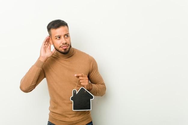 Jovem sul-asiático segurando um ícone em casa, tentando ouvir uma fofoca.