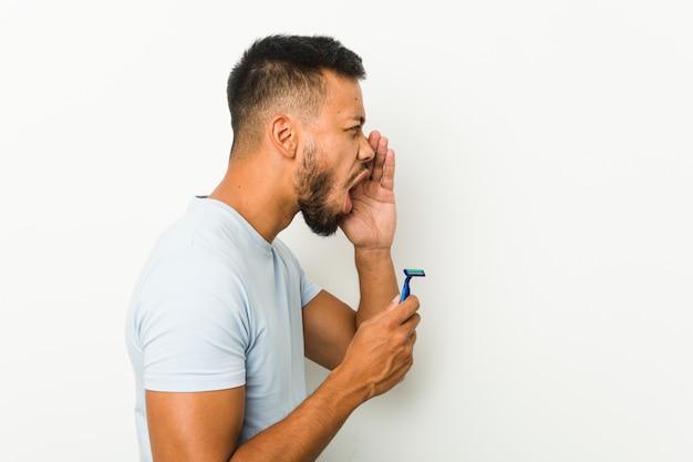 Jovem sul-asiático segurando uma lâmina de barbear gritando e segurando a palma da mão perto da boca aberta