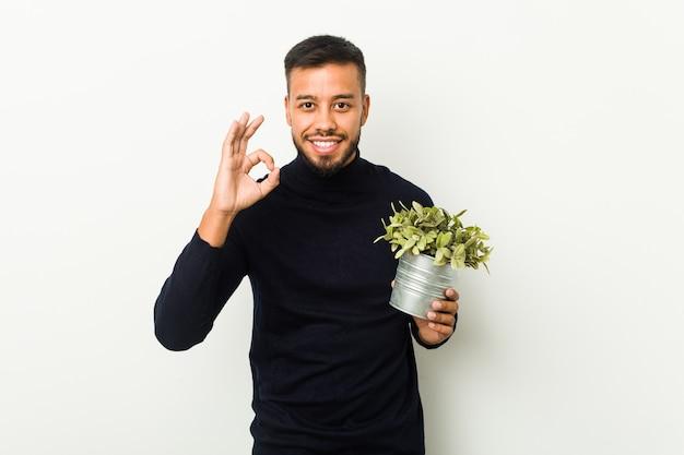 Jovem sul-asiático segurando uma planta alegre e confiante, mostrando um gesto de ok.