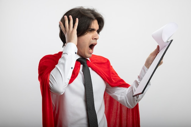 Jovem super-herói assustado usando gravata segurando e olhando para a prancheta colocando a mão na cabeça