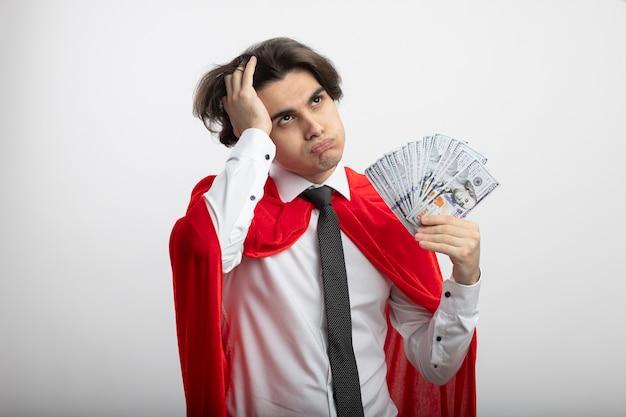 Jovem super-herói cansado olhando para o lado usando gravata, segurando dinheiro e colocando a mão na cabeça isolada no branco