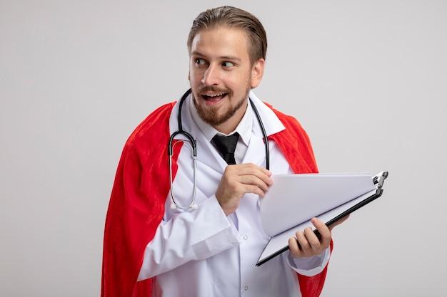 Jovem super-herói ganancioso, olhando para o lado, vestindo túnica médica com estetoscópio folheando a prancheta isolada no fundo branco