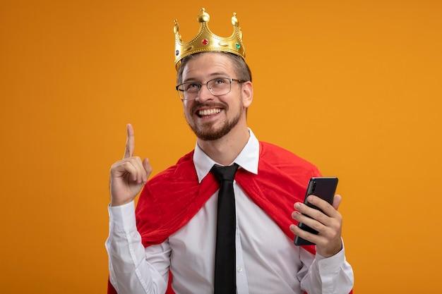 Jovem super-herói impressionado usando gravata e coroa com óculos segurando o telefone e aponta para cima isolado em fundo laranja