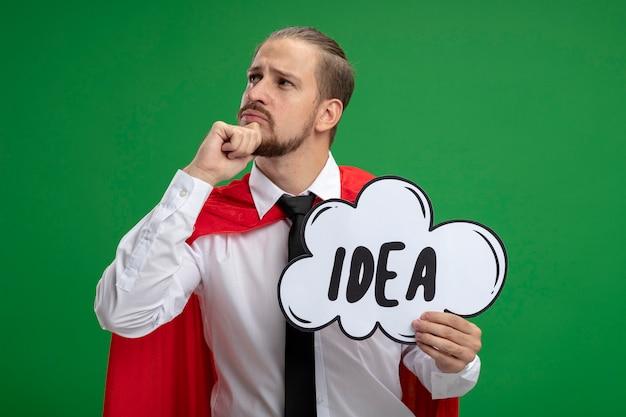 Jovem super-herói pensando olhando para o lado segurando a bolha da ideia e agarrando o queixo isolado no fundo verde