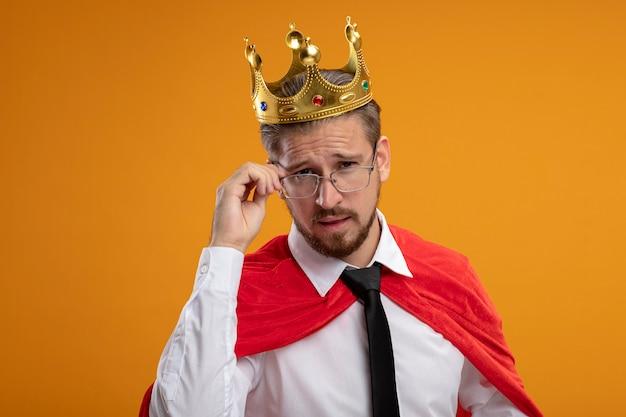 Jovem super-herói pensando usando gravata e coroa usando e agarrou óculos isolados em fundo laranja