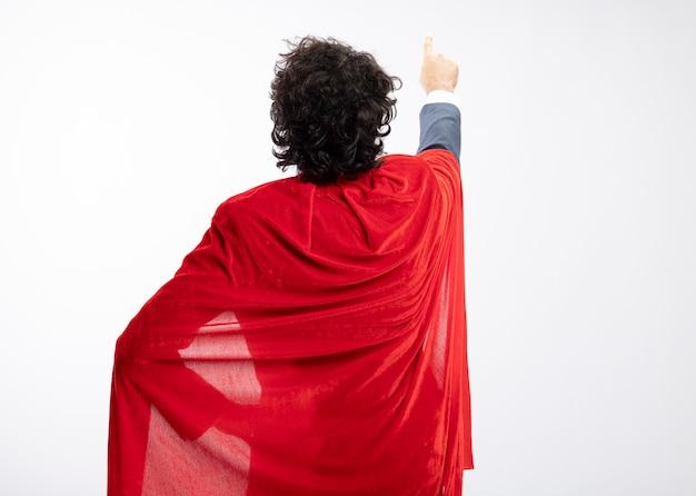Jovem super-herói usando óculos ópticos, usando um terno com capa vermelha, fica de costas para a frente apontando para cima, isolado na parede branca