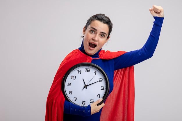 Jovem super-heroína alegre segurando um relógio de parede e mostrando um gesto de sim, isolado no fundo branco
