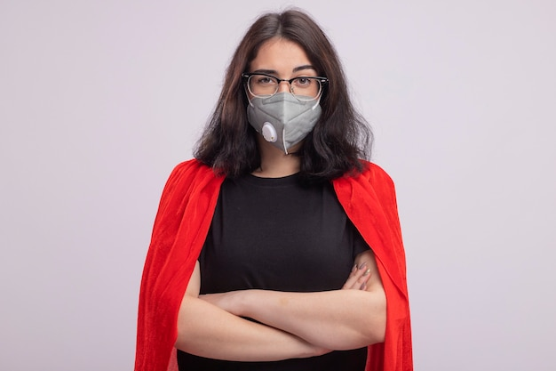 Jovem super-heroína caucasiana confiante com capa vermelha, óculos e máscara protetora