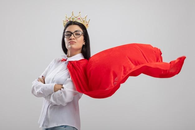 Jovem super-heroína caucasiana confiante usando óculos e coroa em pé com postura fechada em vista de perfil, olhando para a câmera isolada no fundo branco